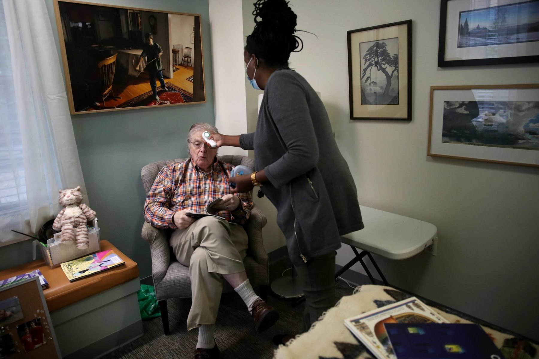 A resident of an assisted living facilty gets his temperature checked.