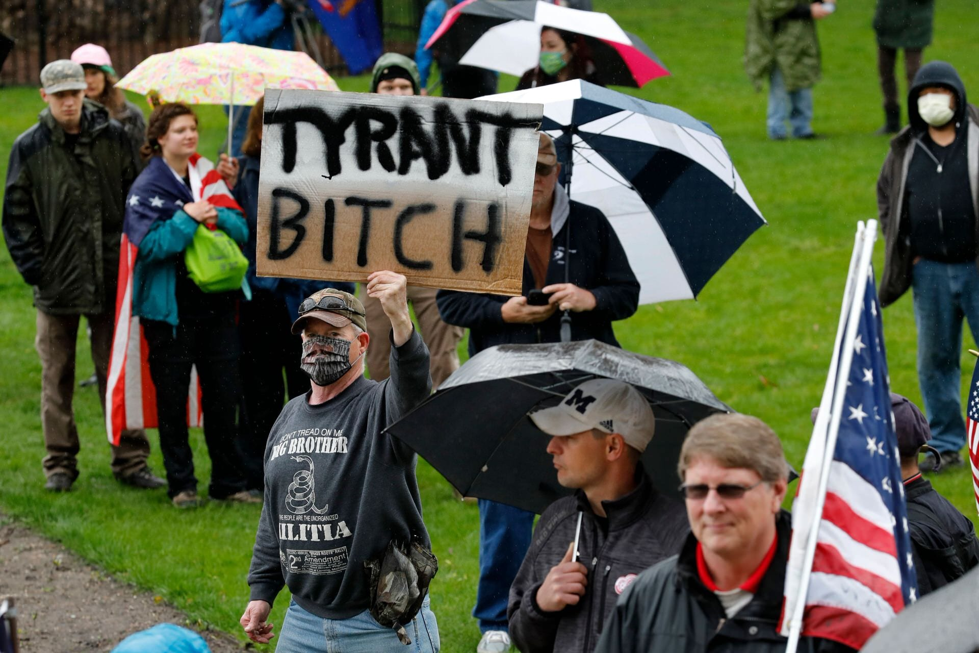 """A man holds a sign with """"tyrant bitch"""" written on it."""