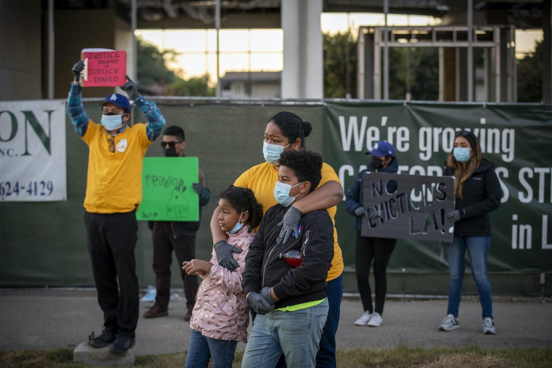 A woman stands with her two kids at a protest.