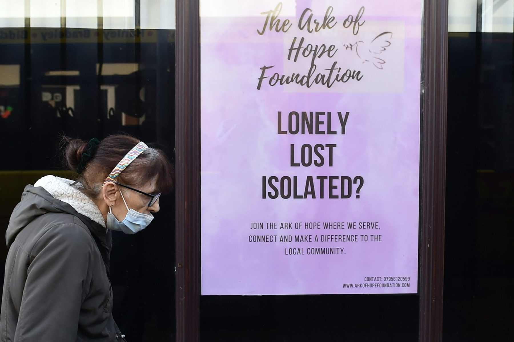 A woman wearing a mask walks past a sign that reads