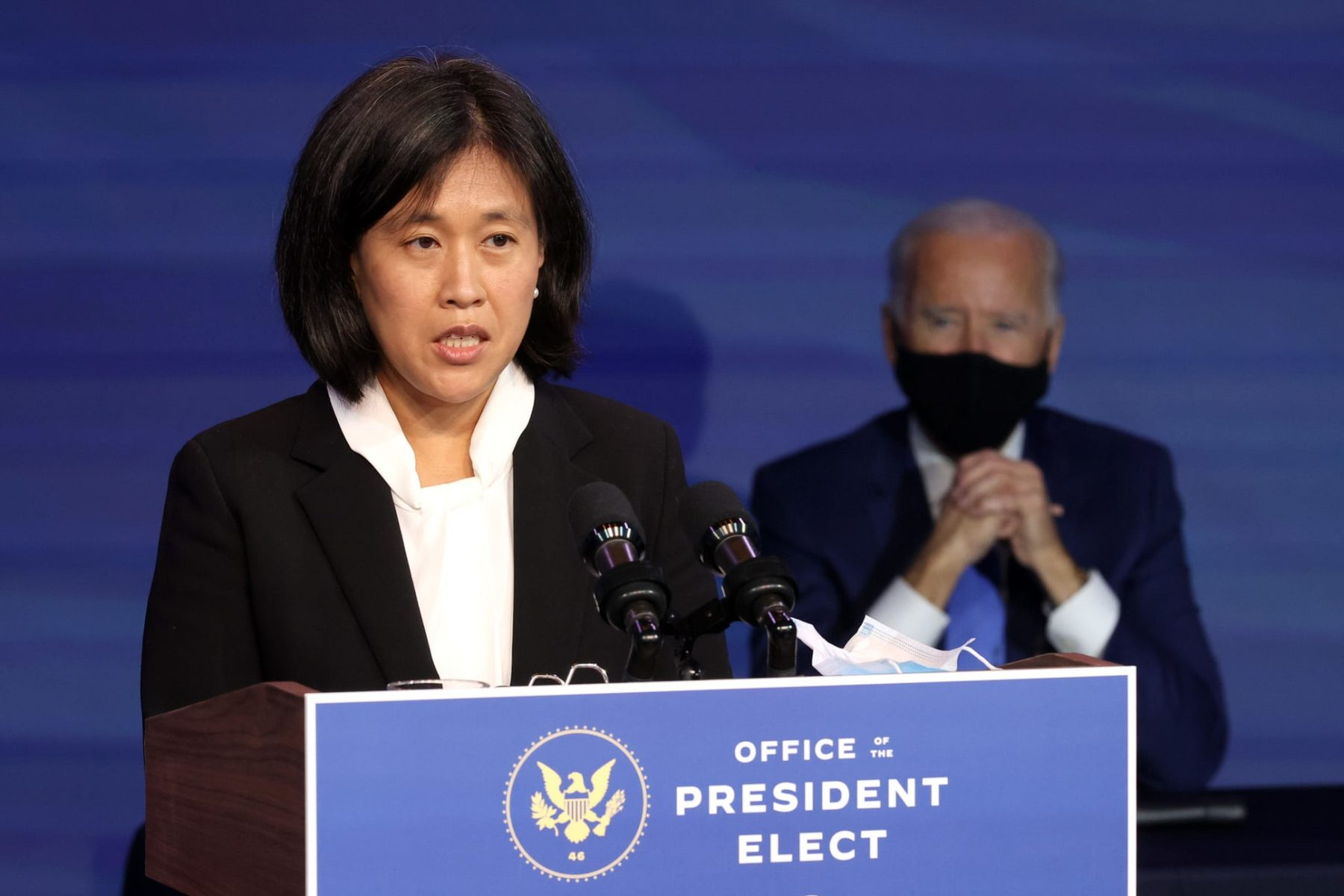 Katherine Tai delivers remarks from a podium with a masked Joe Biden standing behind her.