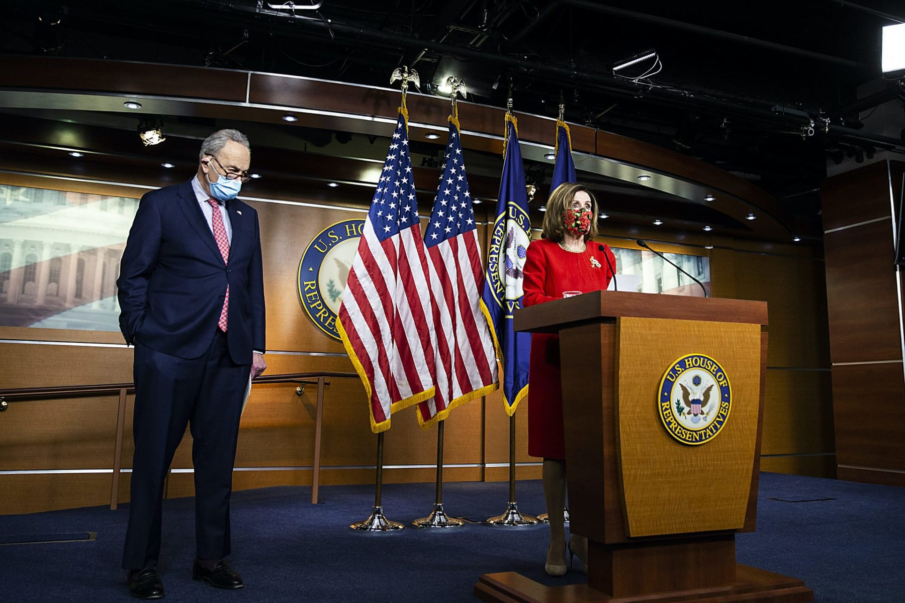 Nancy Pelosi stands at a podium with Chuck Schumer to her right.
