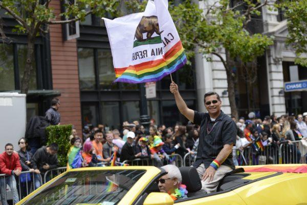 Xavier Becerra riding in a car waving a California flag with the LGBTQ+ rainbow at the bottom.