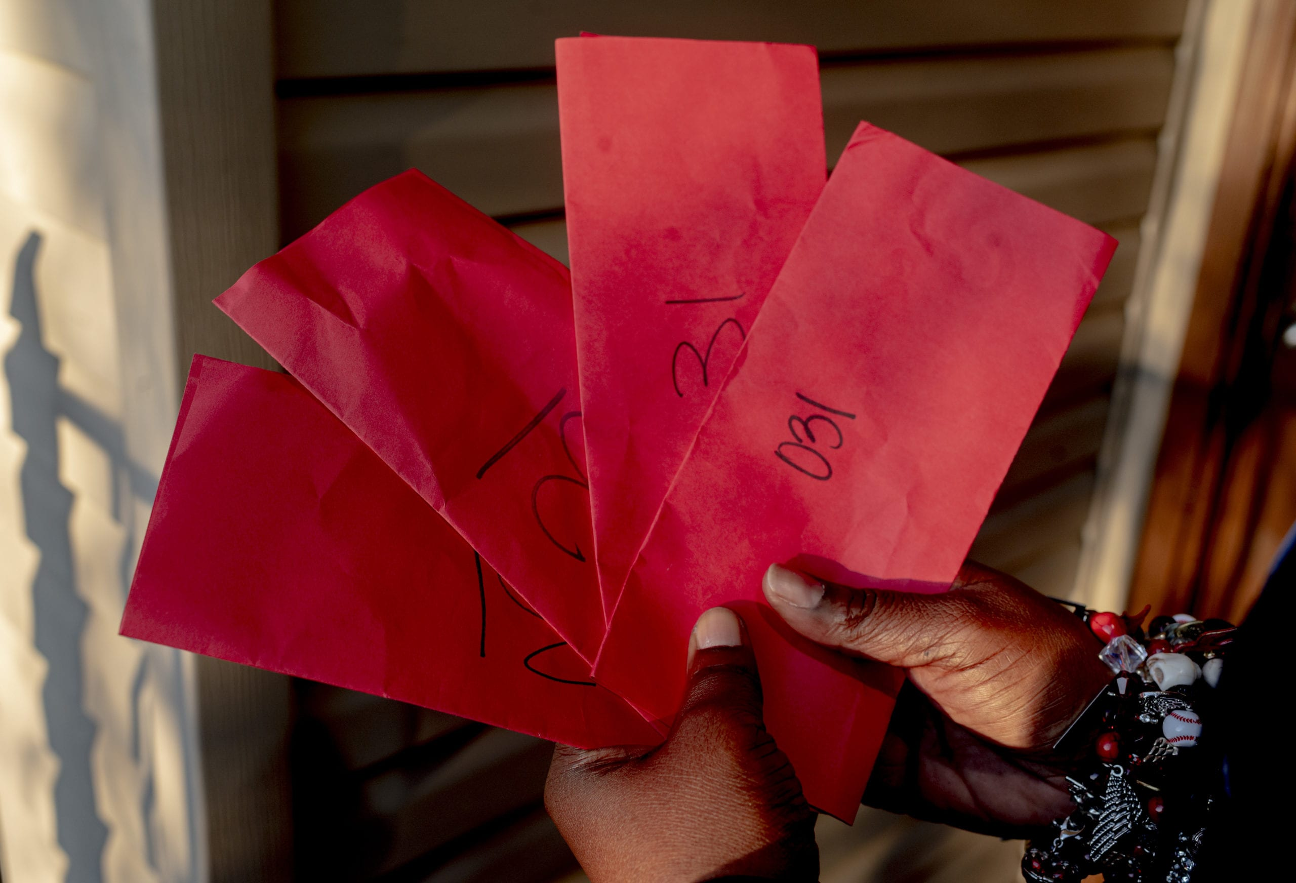 Shanta Scott holds some of the eviction notices, or red slips, she received after losing her job in March 2020.