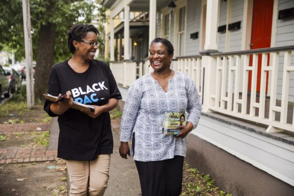 Adrianne Shropshire, executive director of BlackPAC, walking with a canvasser.