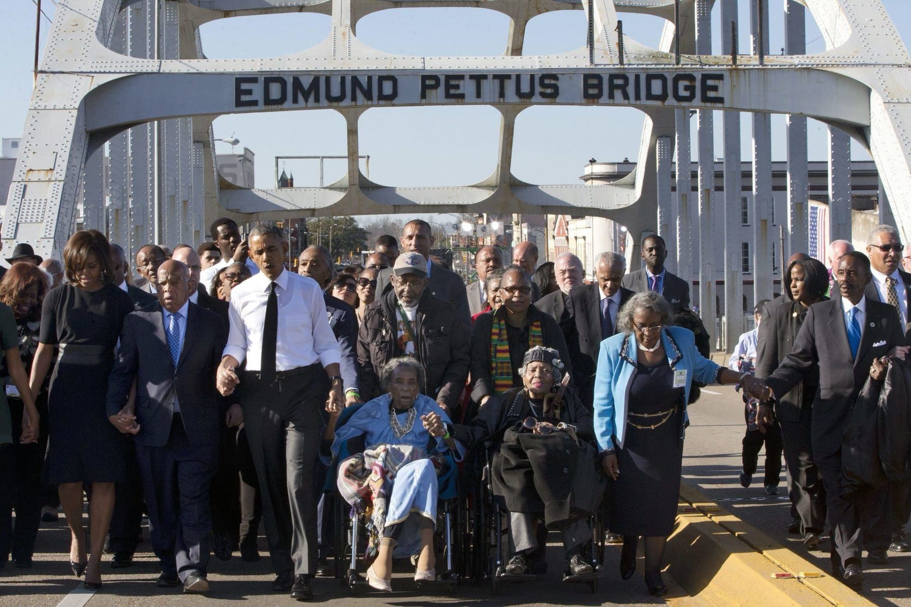 President Barack Obama walks over the Edmund Pettus Bridge with a group on the 50th anniversary of