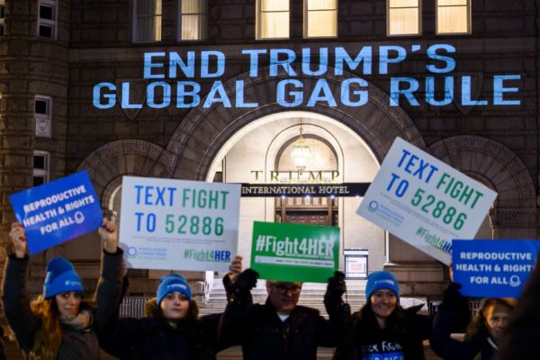 Activists from the Population Connection Action Fund hold signs in front of the Trump International Hotel..