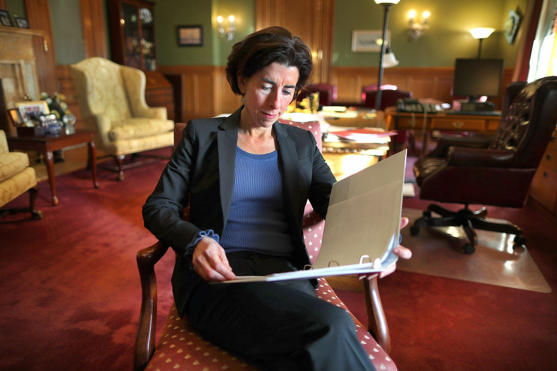 Gina Raimondo reads a document in her office.