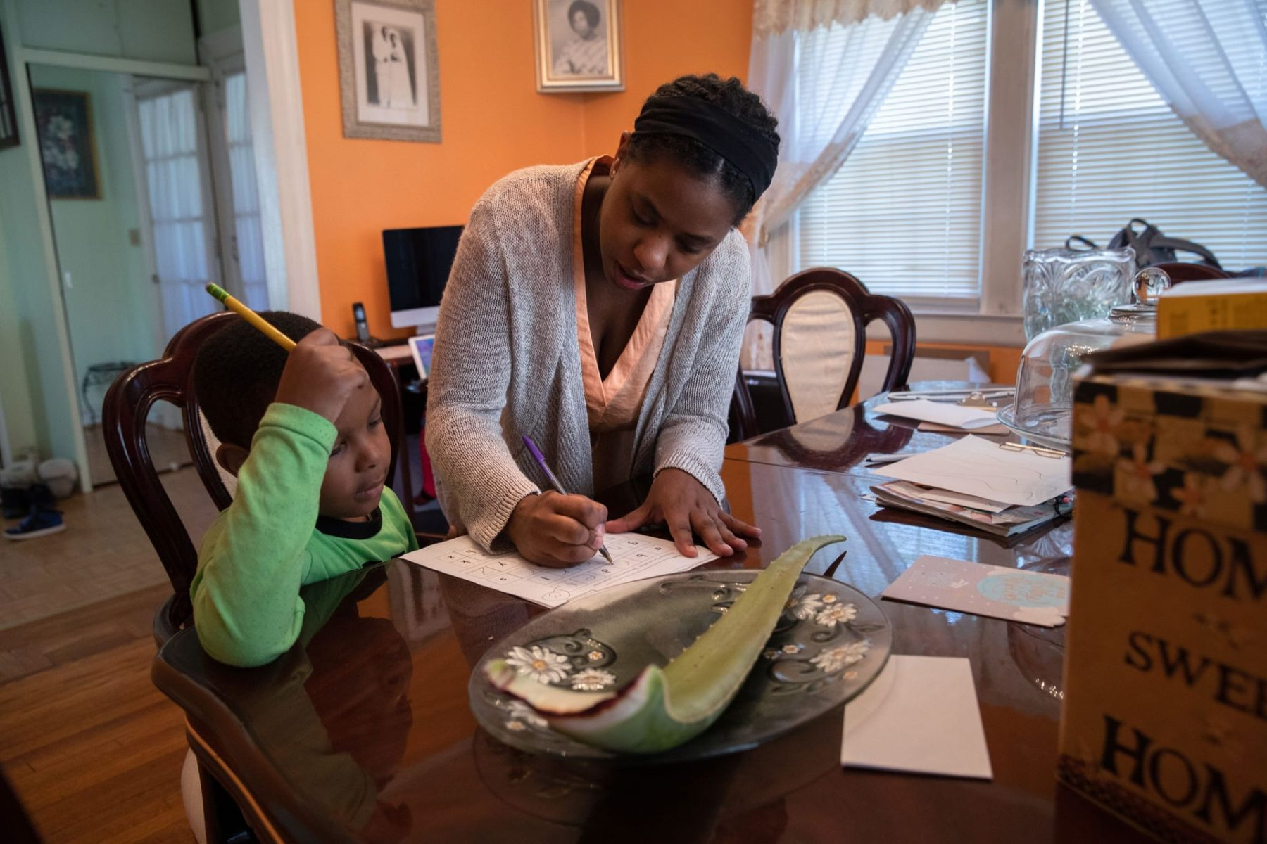 A mother helps her son with his school work at home.