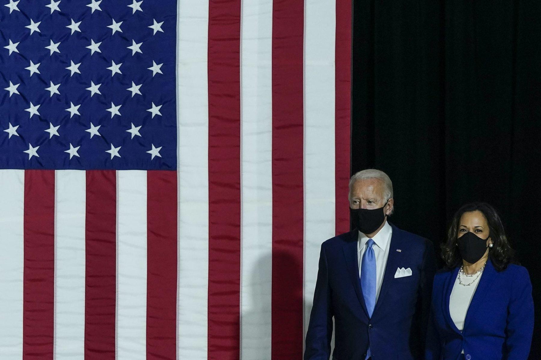 Joe Biden and Kamala Harris, both wearing masks, walk in front of an American flag.