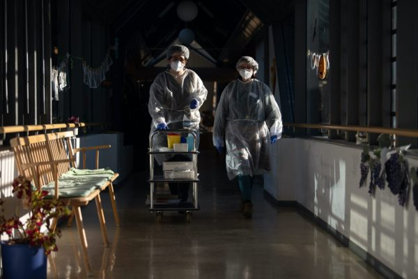 Two geriatric nurses walk through a corridor in the Pauline Krone Home for the Elderly of the Tübingen elderly care centre with protective equipment that they have put on to carry out rapid antigen-corona tests. (