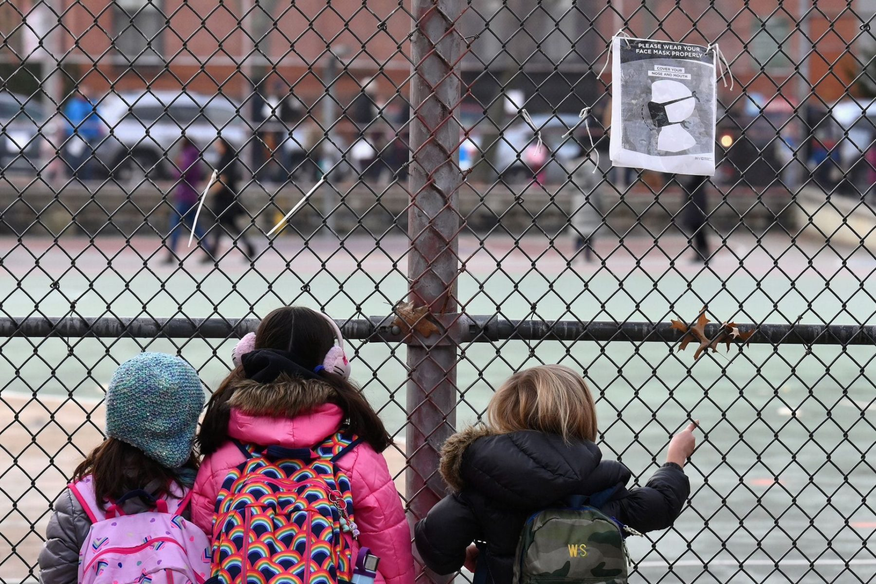 A group of children look at their school ground through a fence.