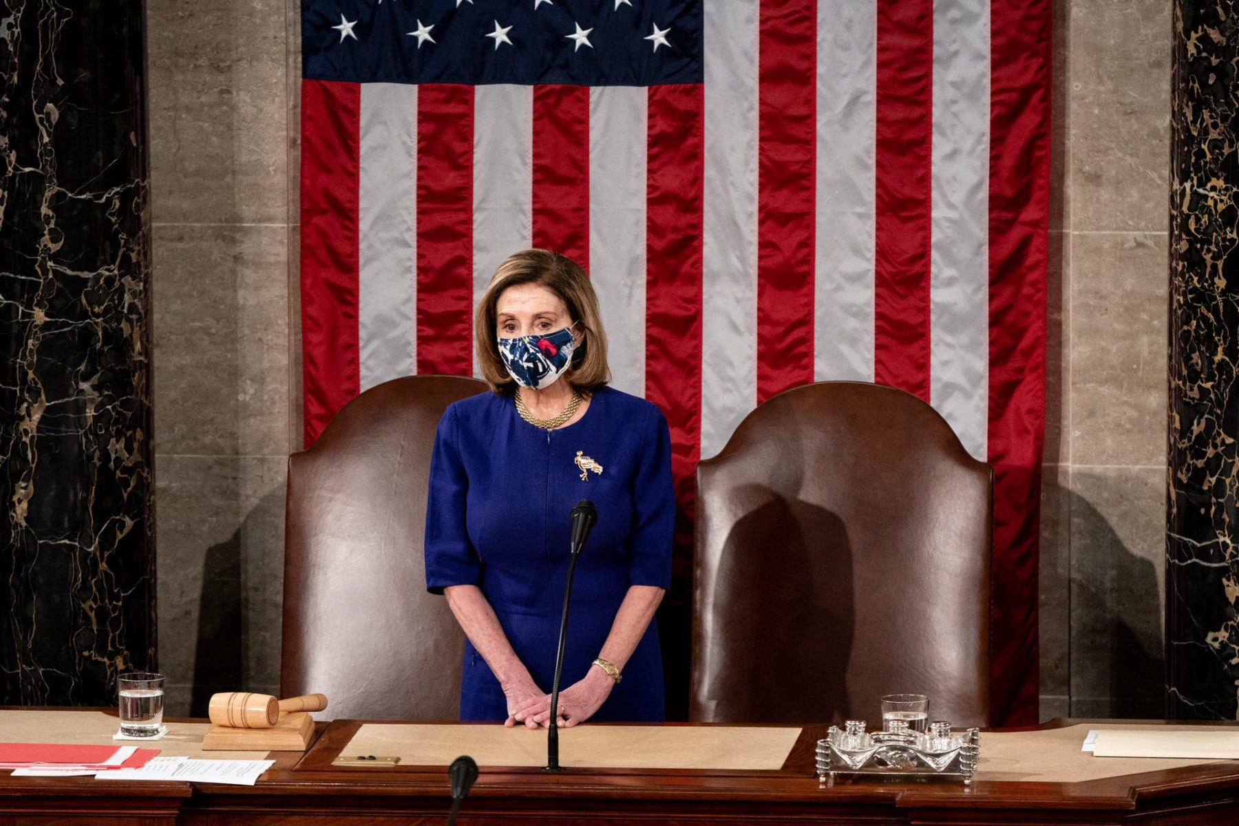 House Speaker Nancy Pelosi waits at the podium in a joint session of Congress.
