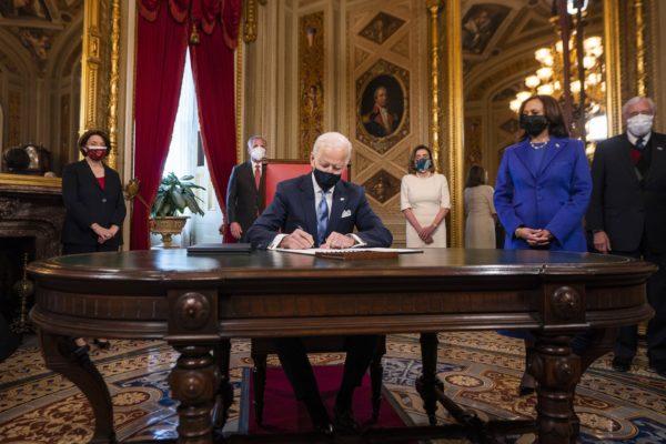US President Joe Biden signs three documents at a table.