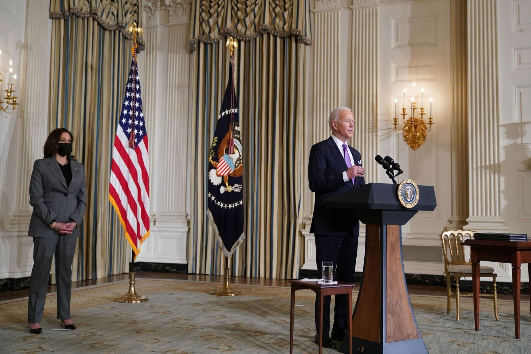 US Vice President Kamala Harris listens as US President Joe Biden speaks on racial equity at a podium in the White House state dining room.