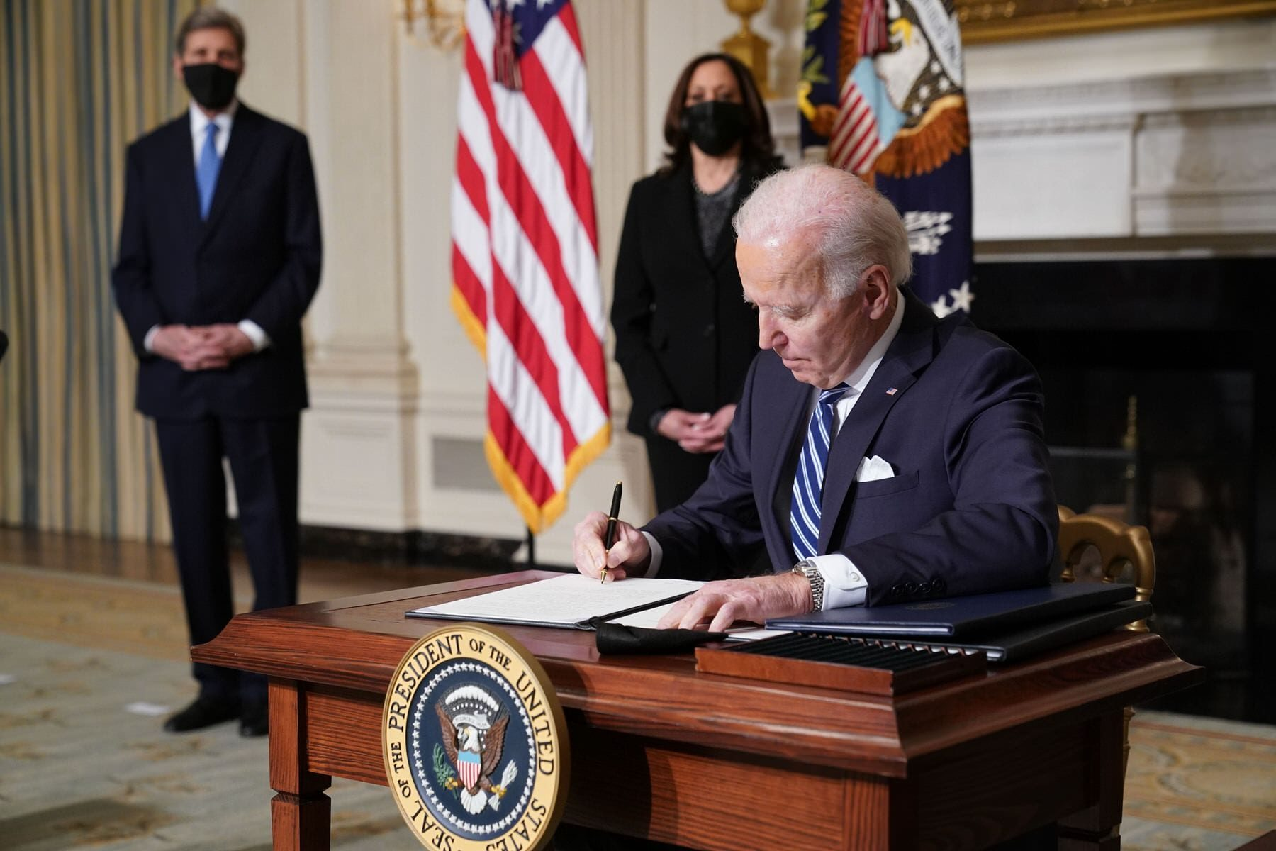 US Vice President Kamala Harris and Special Presidential Envoy for Climate John Kerry watch as US President Joe Biden signs executive orders.
