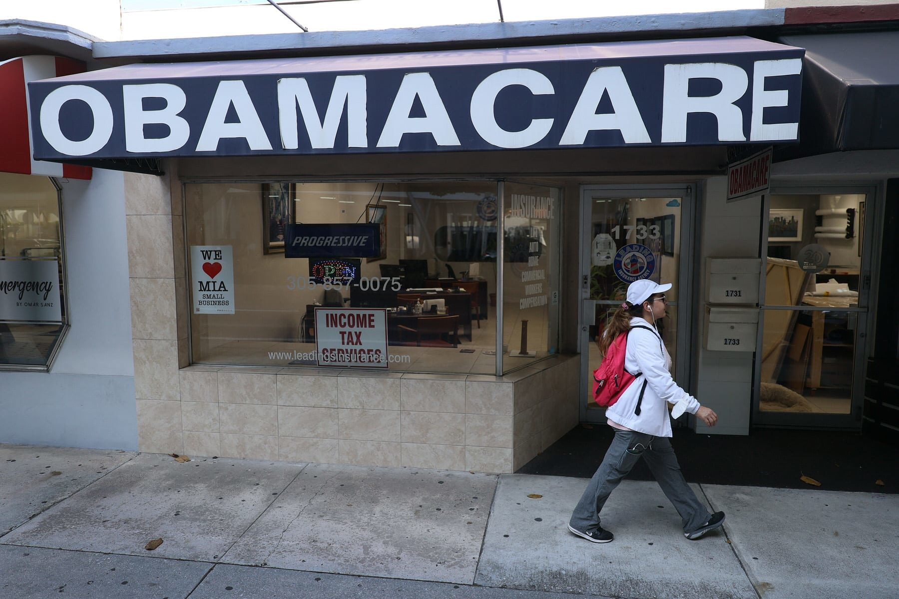 A woman walks past a lending agency with a large Obamacare sign.