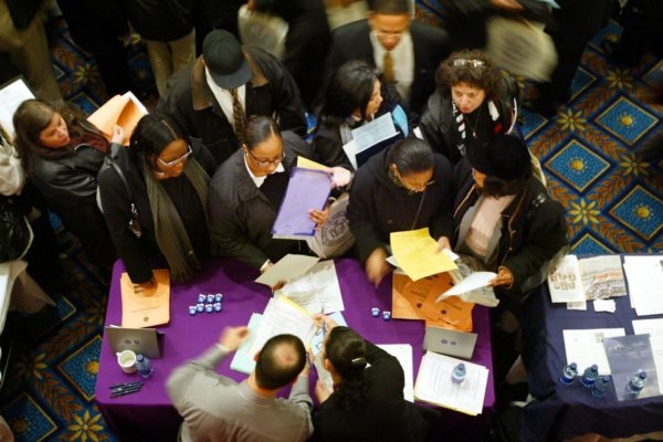 Job applicants gather around an employers table at Hispanic job fair.