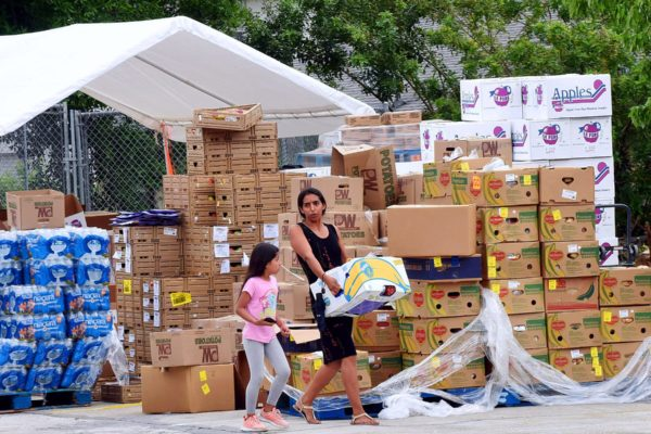 A woman with a child carries a box of food.