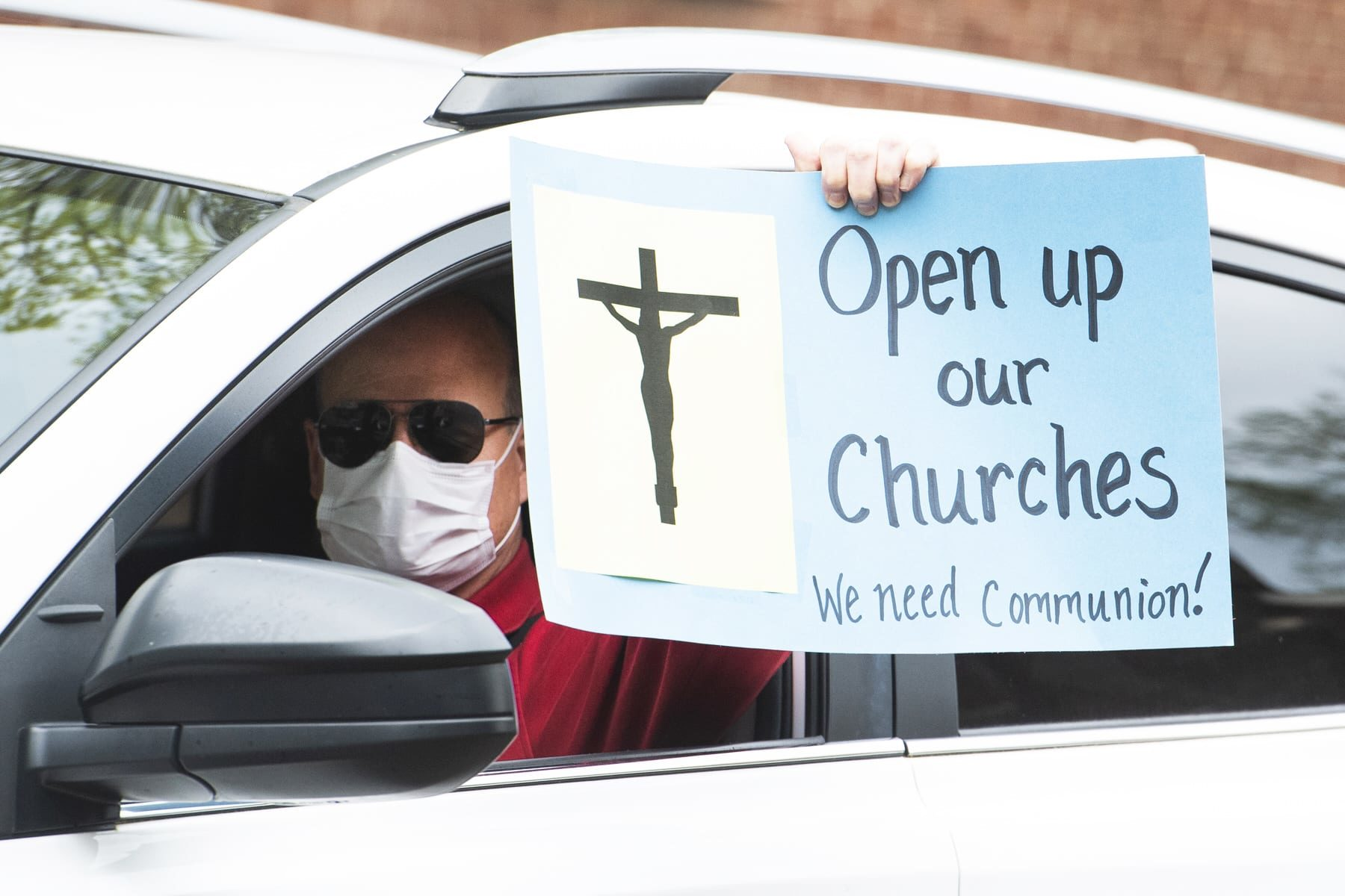 A demonstrators holding a sign out of a car window demanding restrictions that have closed churches be lifted.