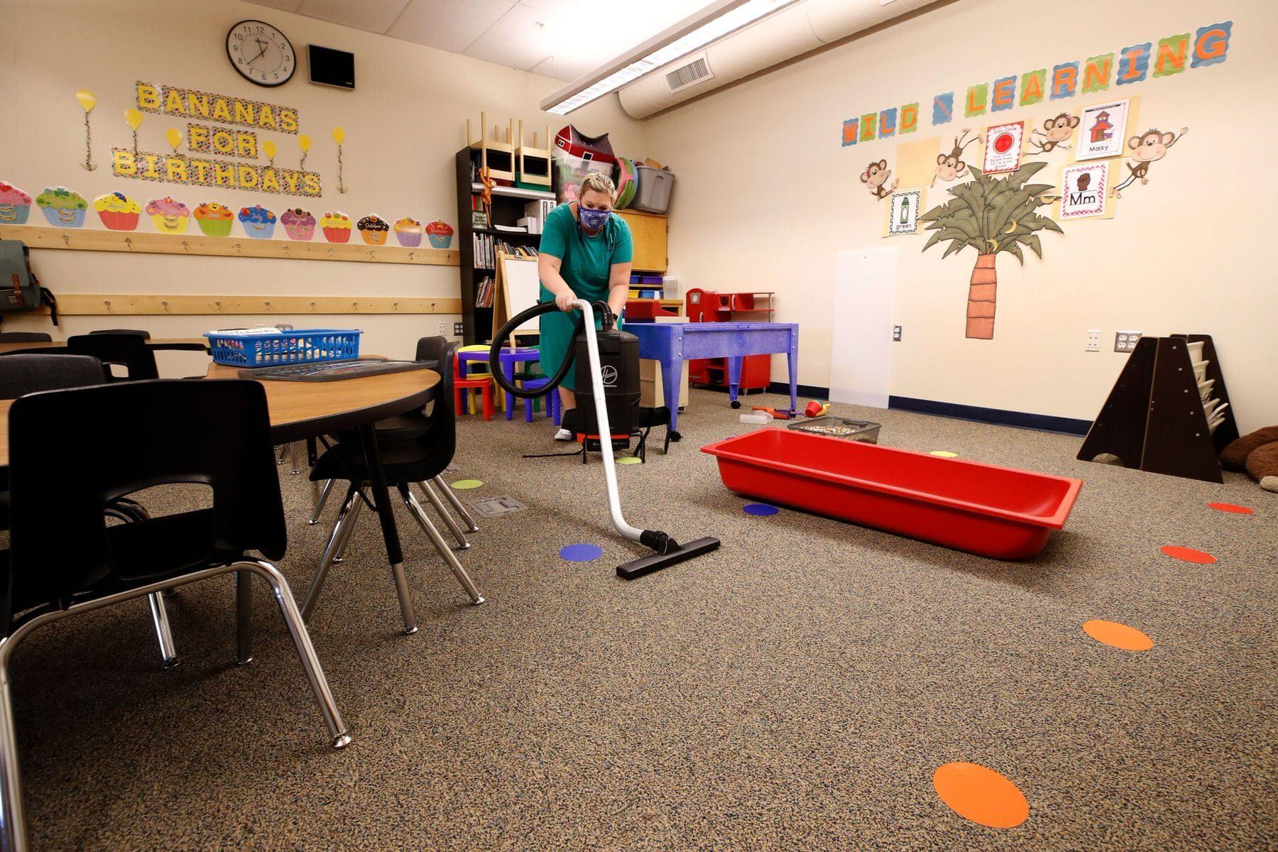A teacher cleans her classroom.