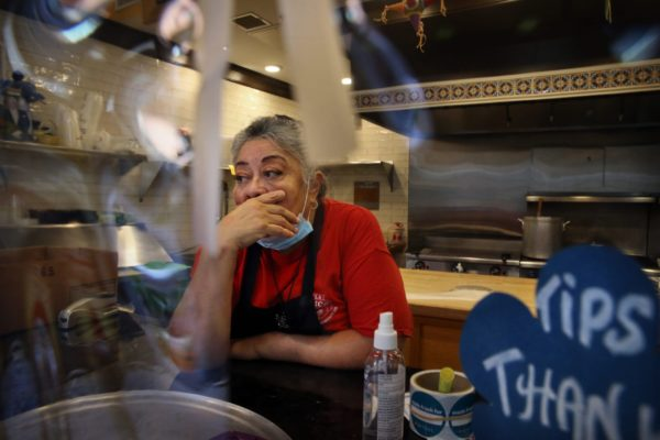 Owner Julie King, in a red shirt covered by an apron, holds back tears at Villa Mexico Cafe on Water Street in Boston, MA. A customer had just walked out while she was on the phone with another customer who was trying to negotiate the price of an order. Having lost two customers in a matter of minutes she said,