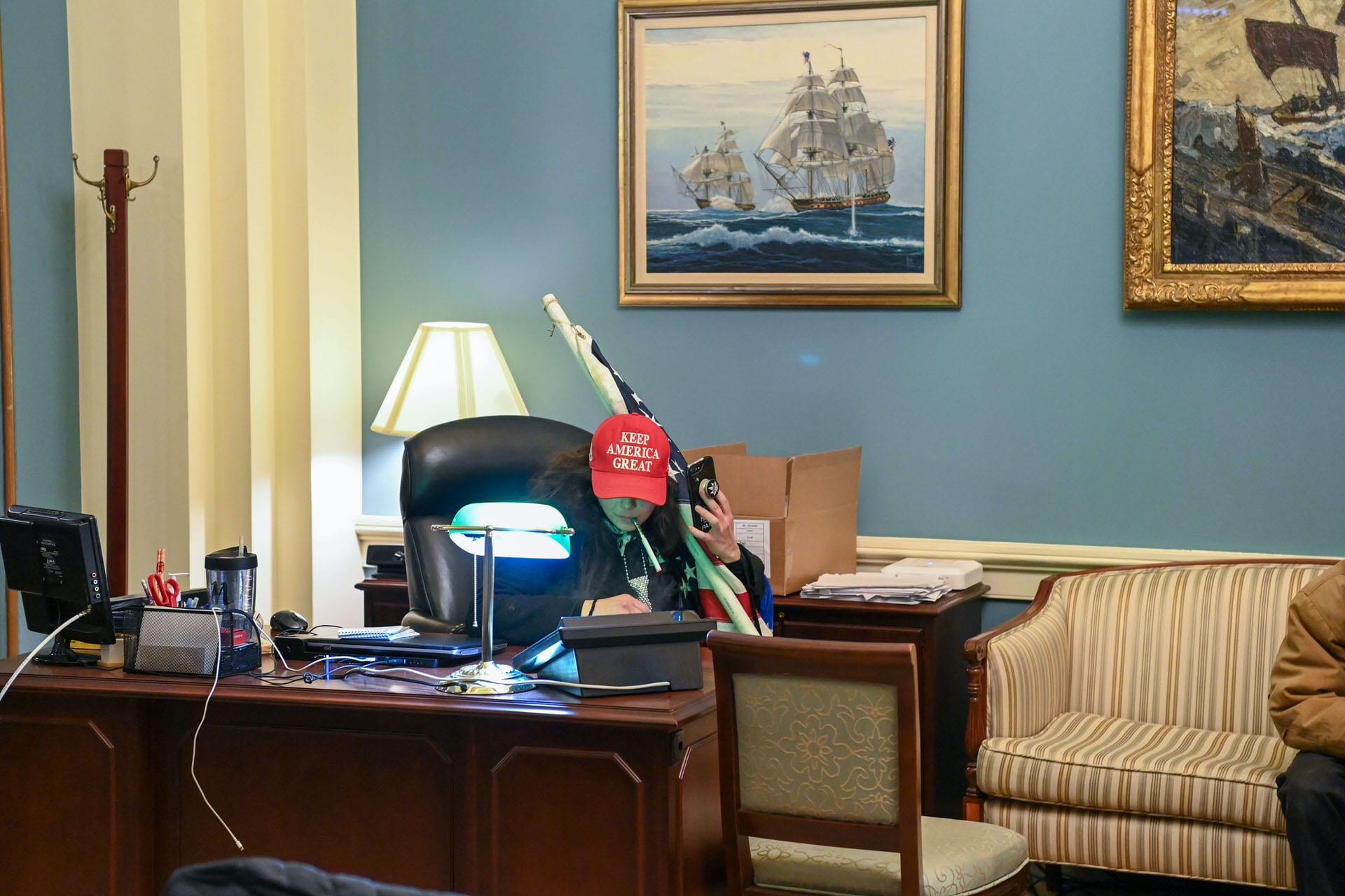 A woman sits at the desk of House Speaker Nancy Pelosi wearing a Make America Great Again hat.