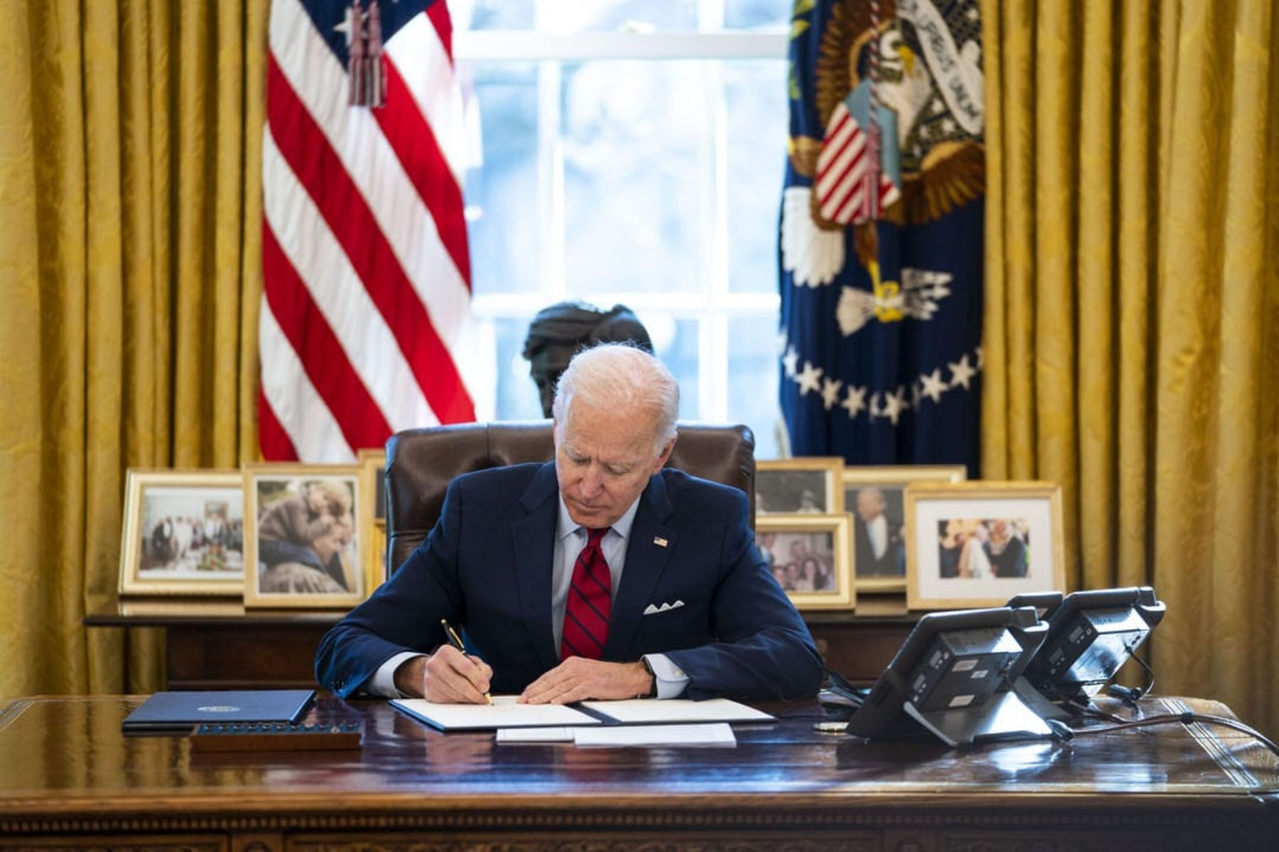 U.S. President Joe Biden signs a series of executive actions at his desk.