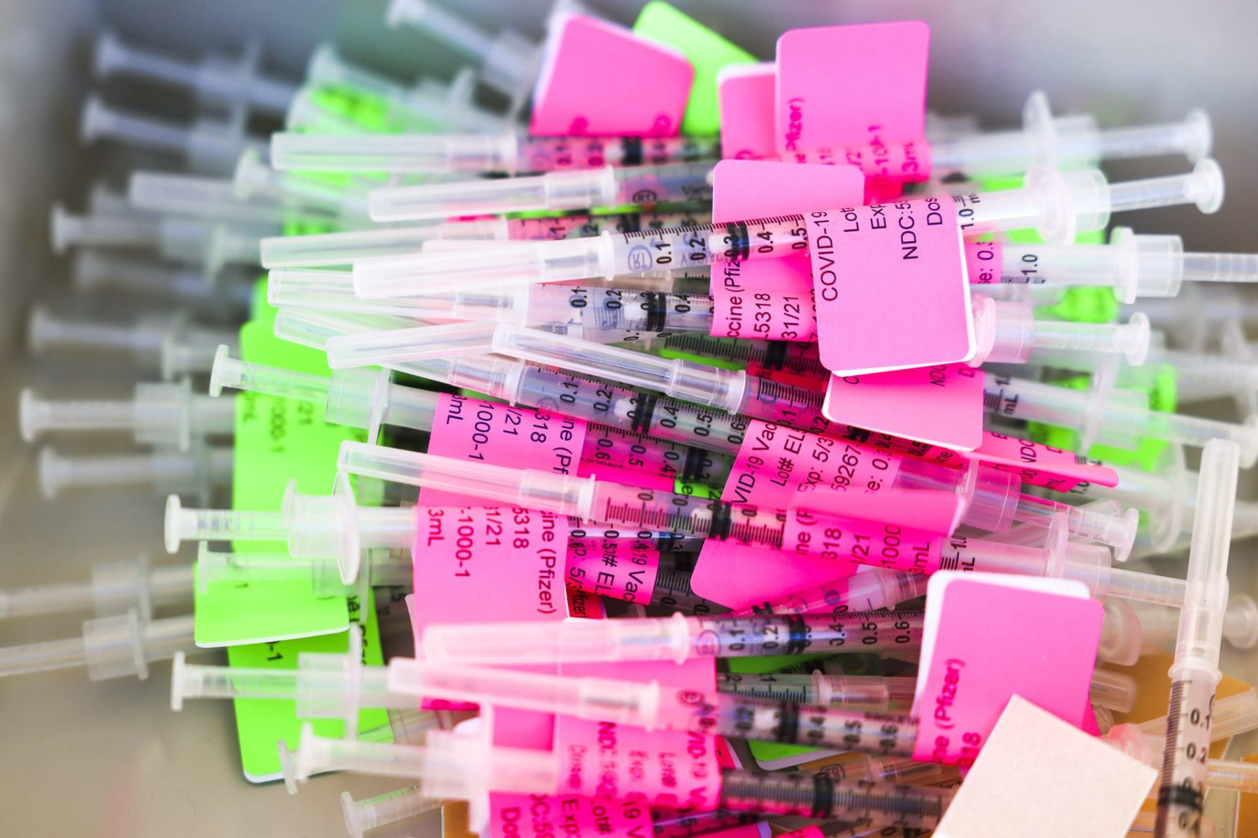 Unused doses of the COVID vaccine in a pile with bright pink and green labels.