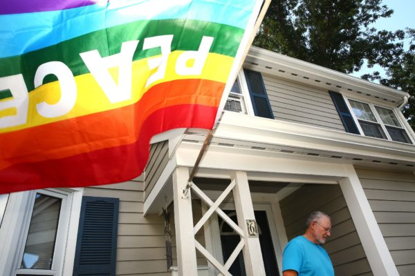 LGBTQ+ flag flying in front of a home.
