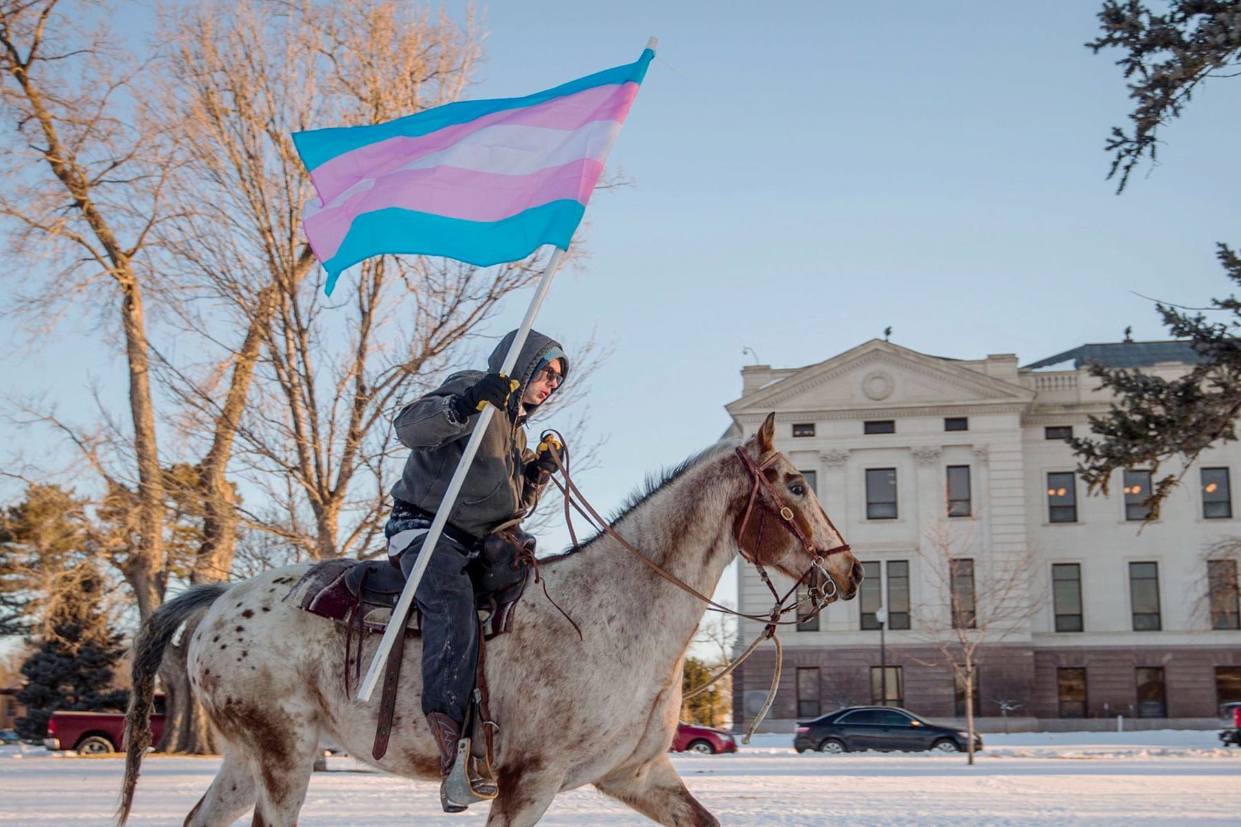 A person rides past the South Dakota Capitol with a trans flag.