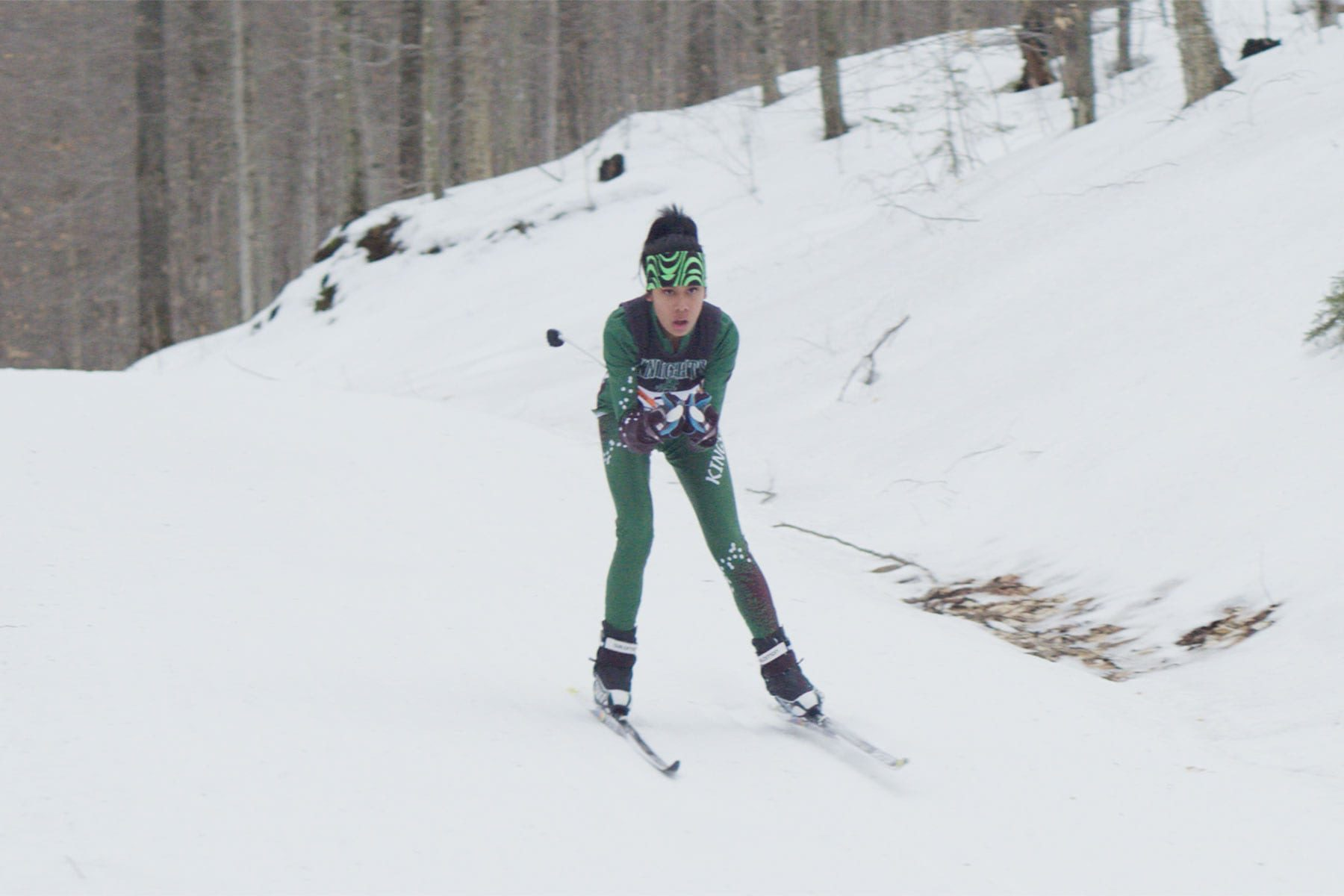 A girl skiing in a snowy forest.