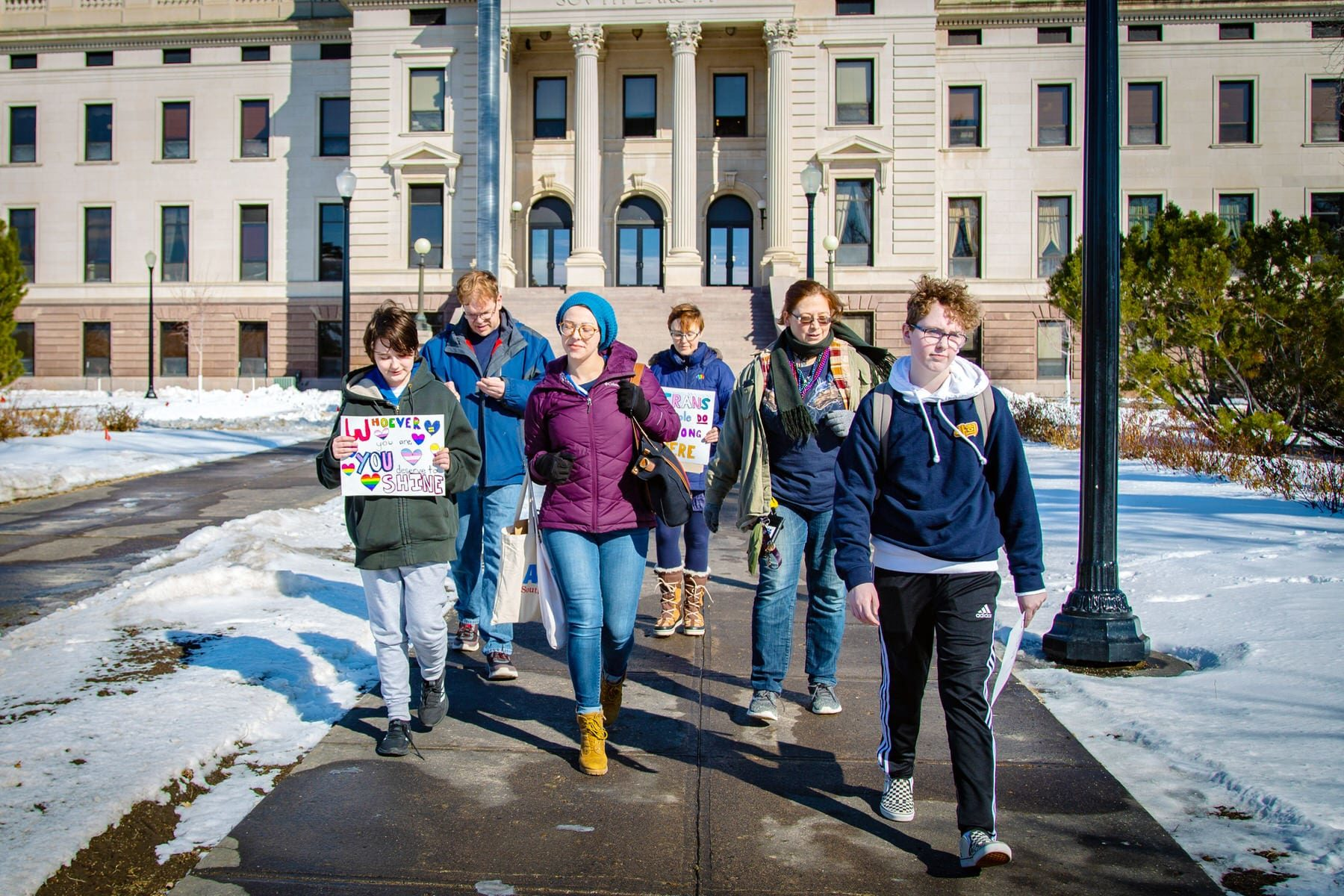 A group of trans youth walk in front of the South Dakota Capitol.