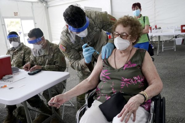 A woman gets her first does of the Pfizer COVID-19 vaccine at a FEMA vaccination site in Florida.