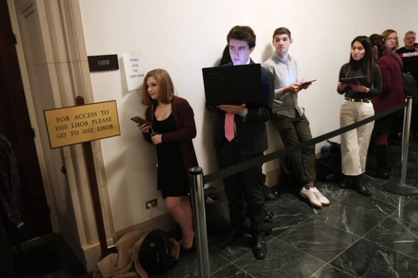 Congressional intern, Sydni Nadler, left, waits in line with others prior to a House Judiciary Committee Impeachment Inquiry hearing.