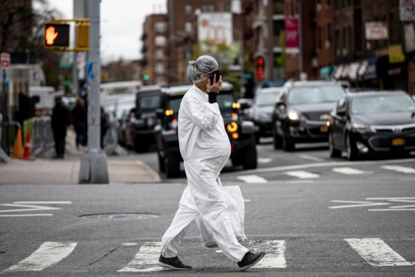 pregnant woman wearing a hazmat suit and a mask walks in the streets in the Elmhurst neighbourhood.
