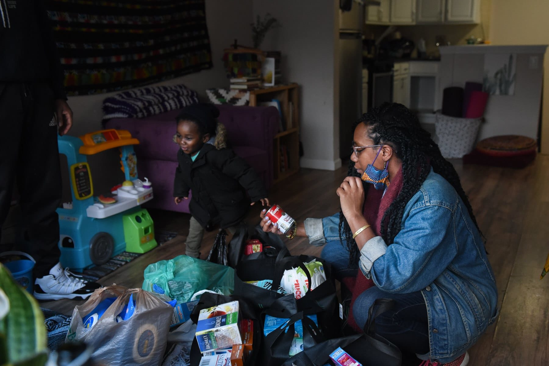 A woman looks at food and essential items as her child plays in the family room.