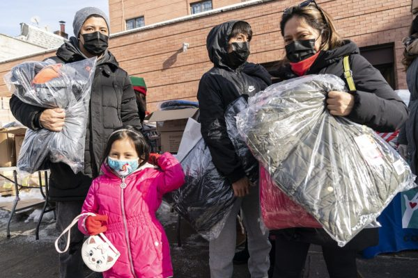 New York Cares volunteers work with a local non-profit organization to distribute toys and winter coats in Corona, Queens.