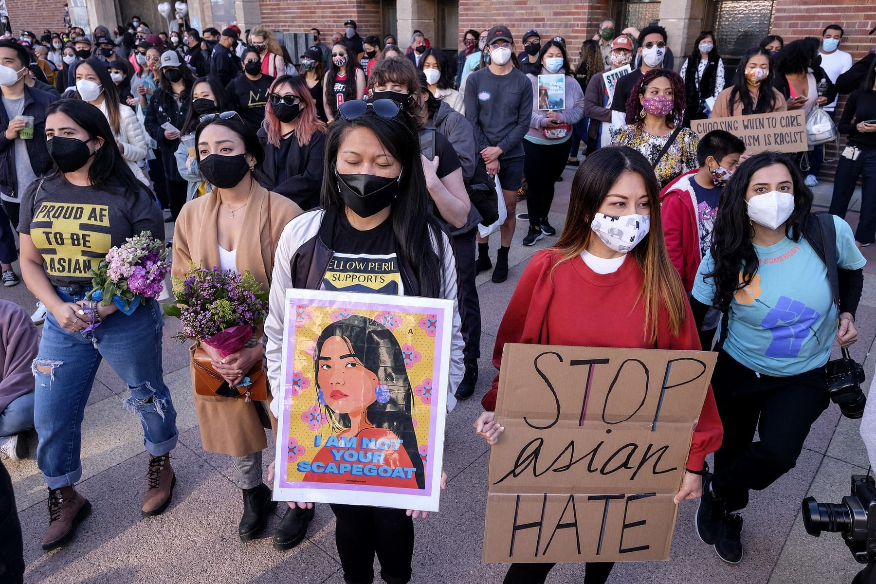 Demonstrators wearing face masks and holding signs take part in a rally