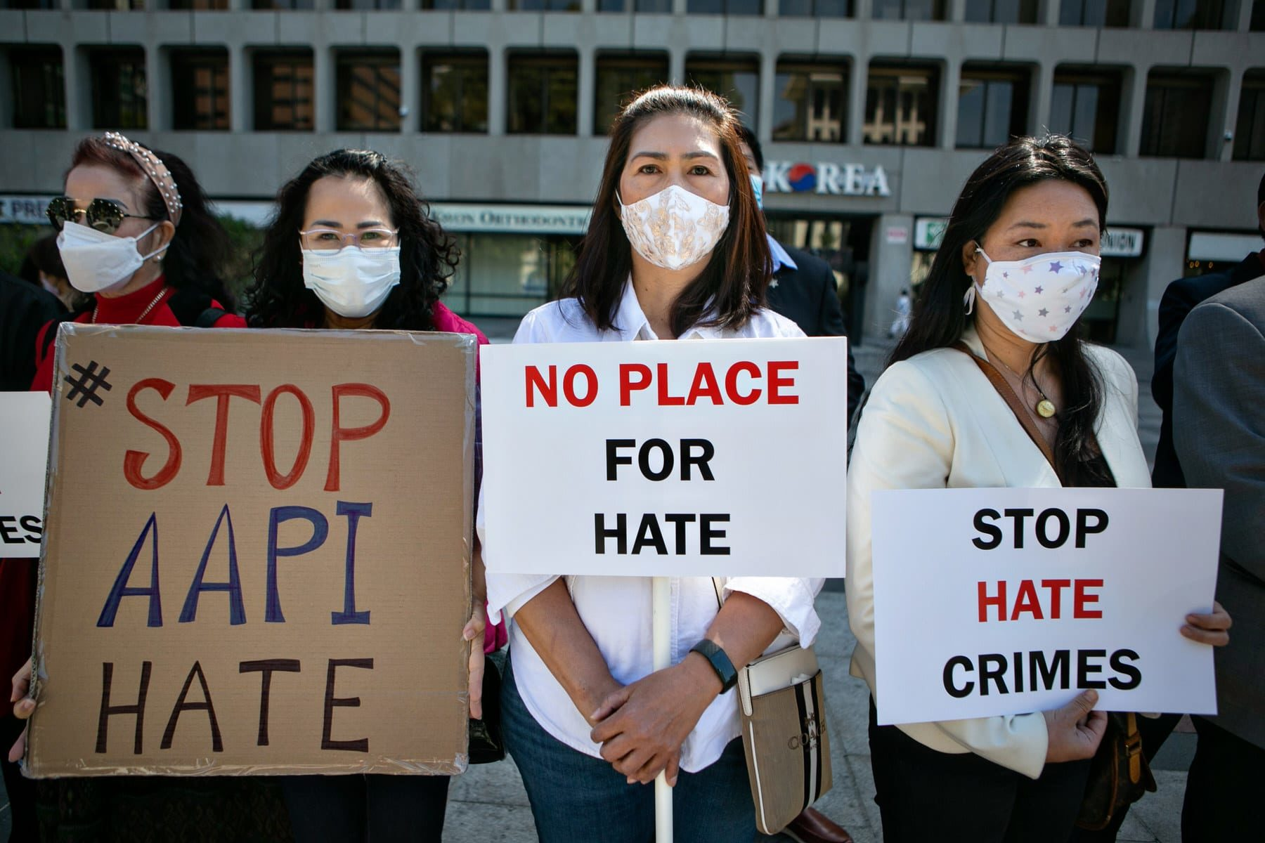 Asian community members hold signs calling for hate to stop.