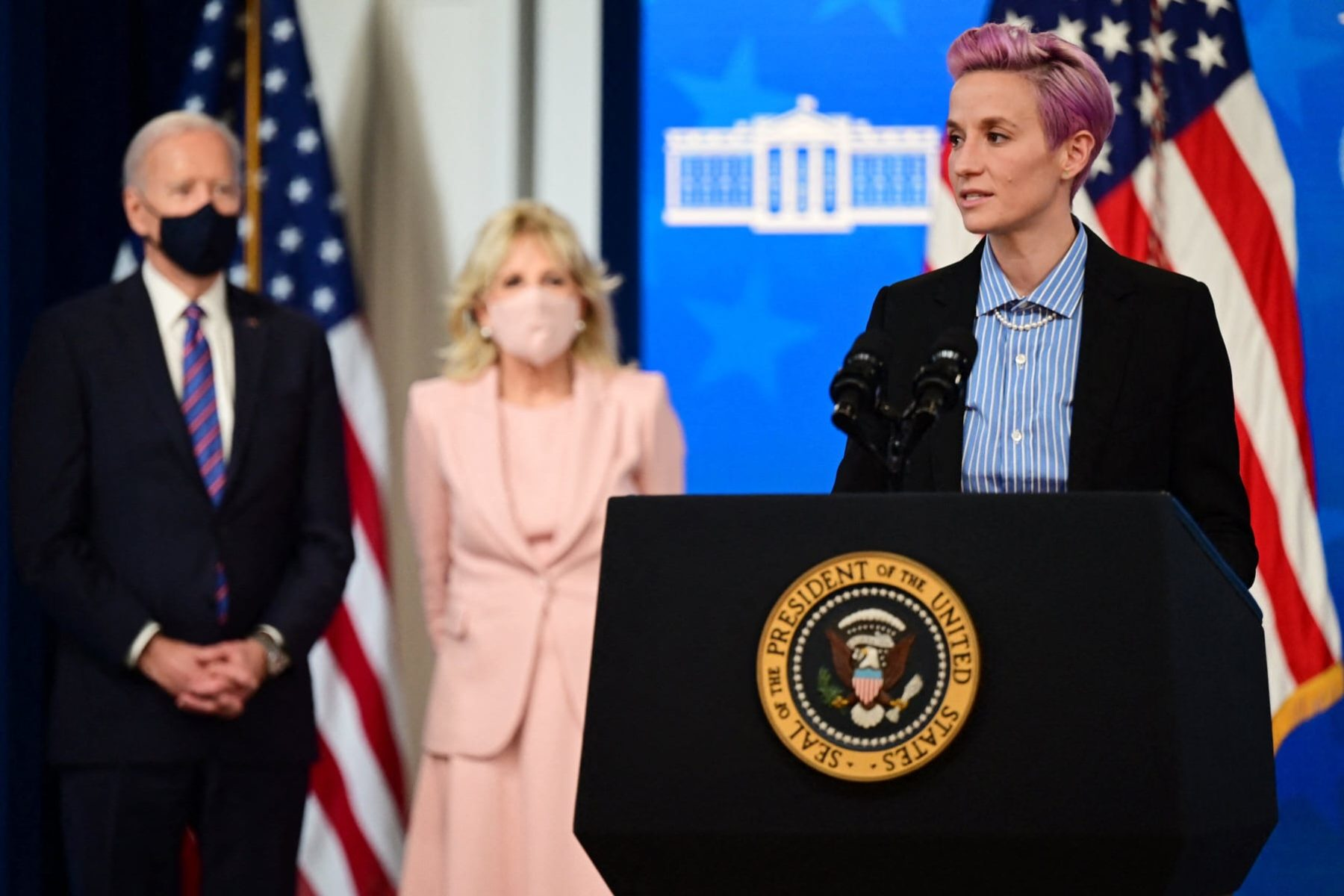 US soccer player Megan Rapinoe (R) speaks, flanked by US President Joe Biden (L) and First Lady Jill Biden during an Equal Pay Day event.