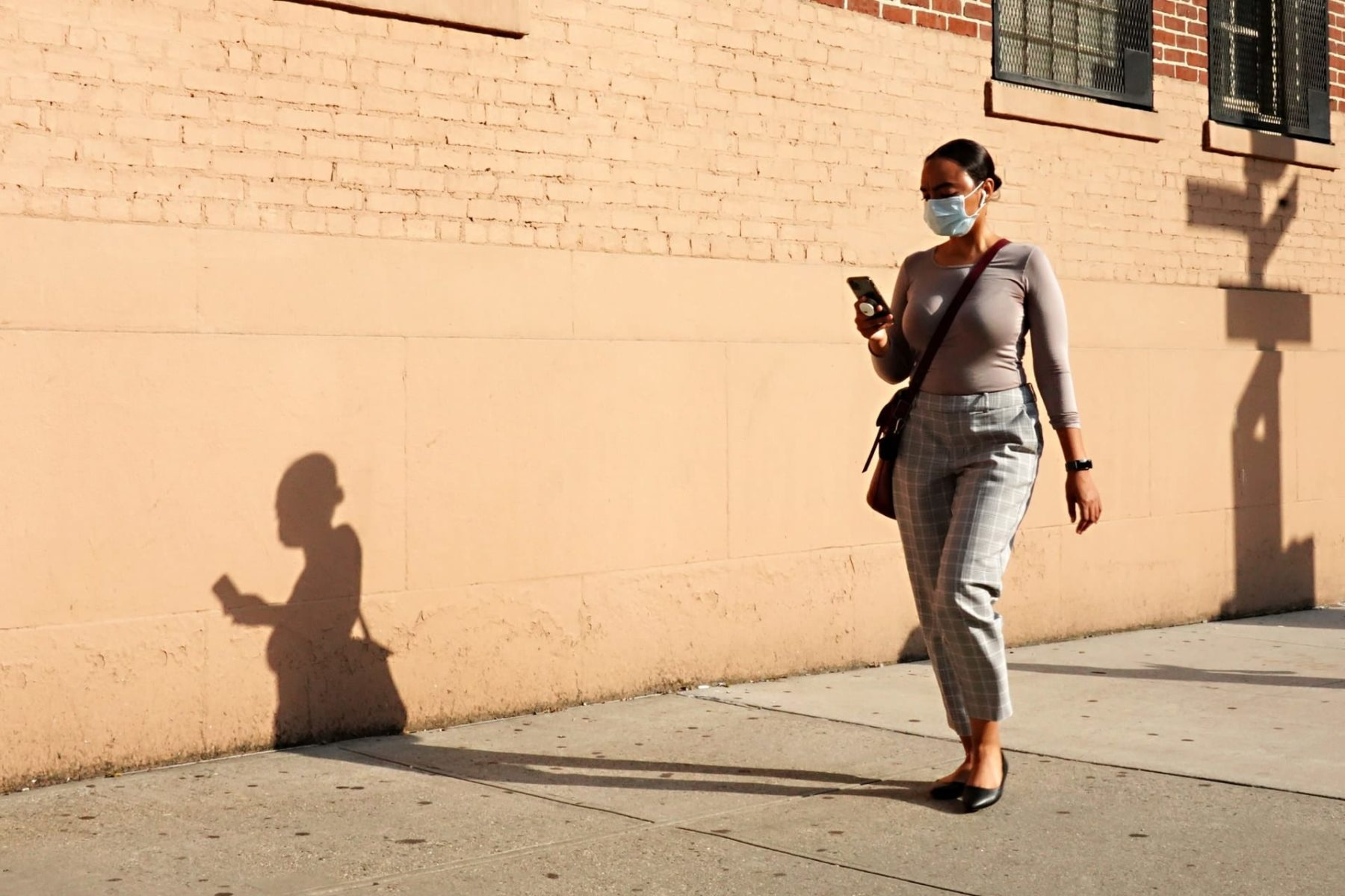 A woman walking down a street in NYC with a mask on looking at her phone.