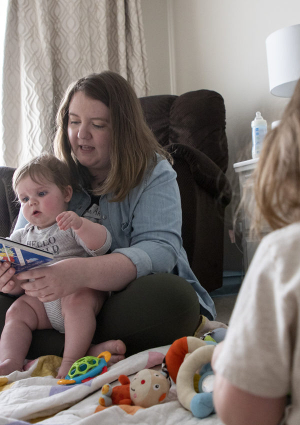 A mother reads to her children in a room.