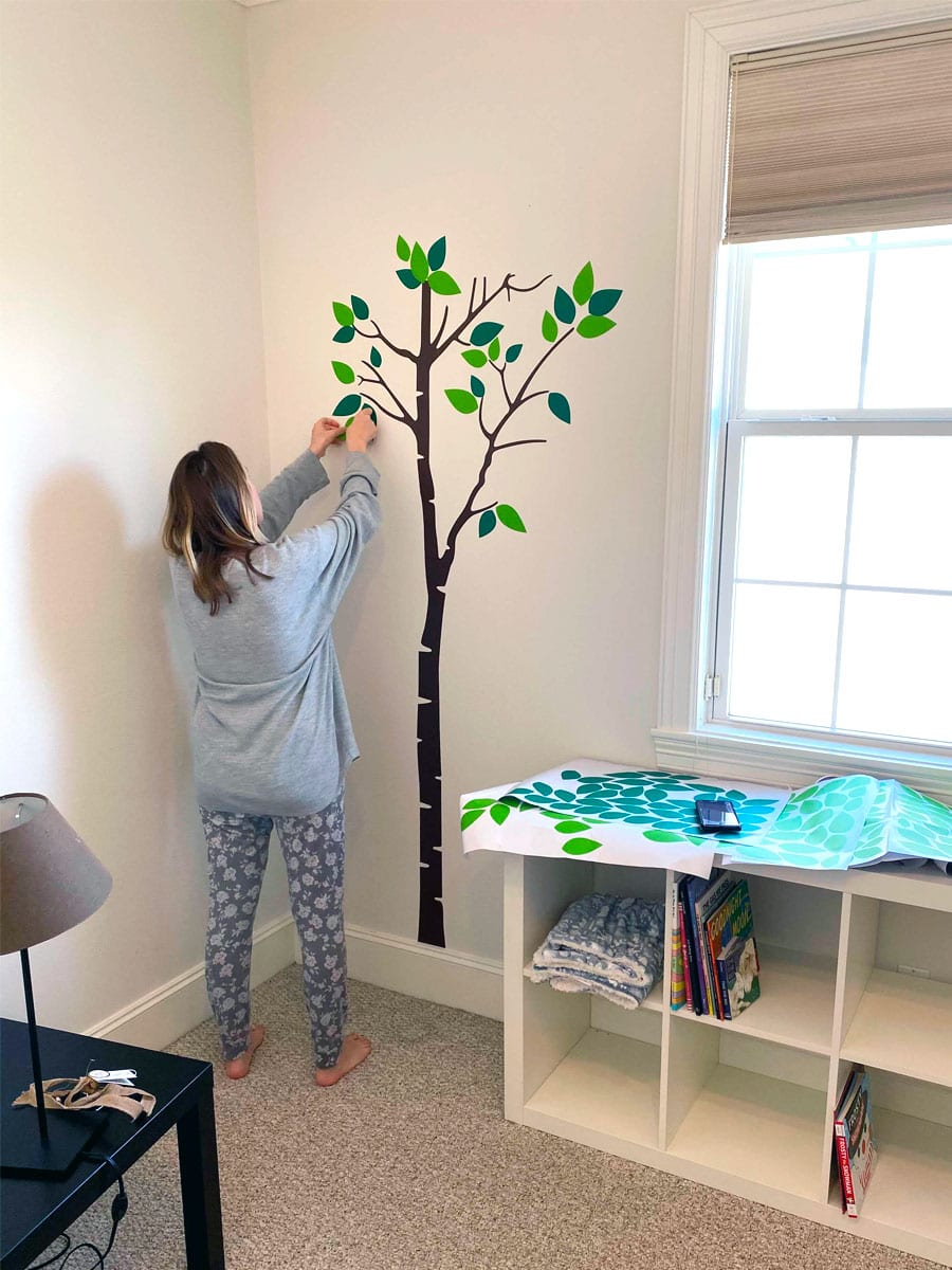 Houston council member Abbie Kamin putting up a wall mural in a nursery.