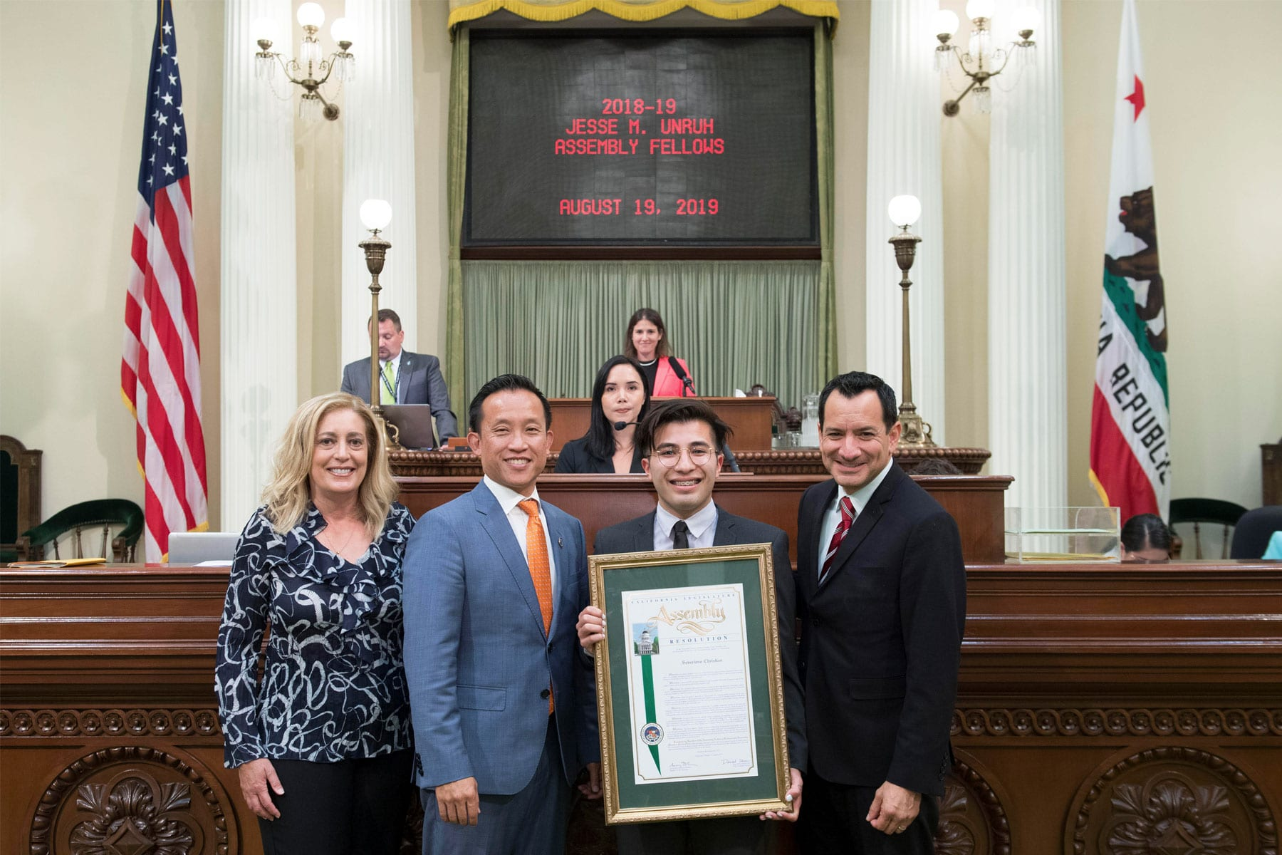 Severiano Christian standing in front of the chamber podium holding am assembly certificate with fellow assembly members.