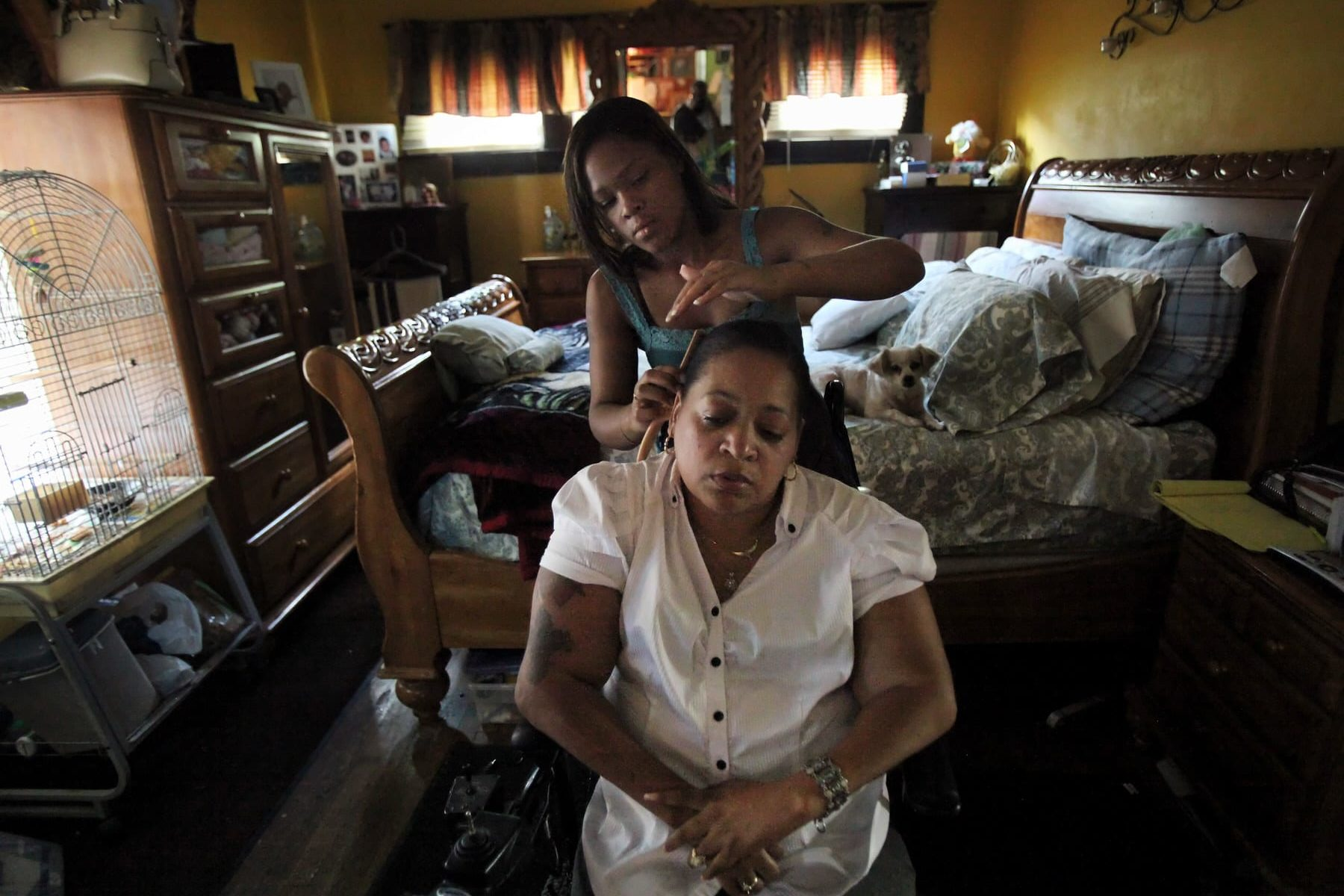 A home health aide brushes the hair of a patient in her home.