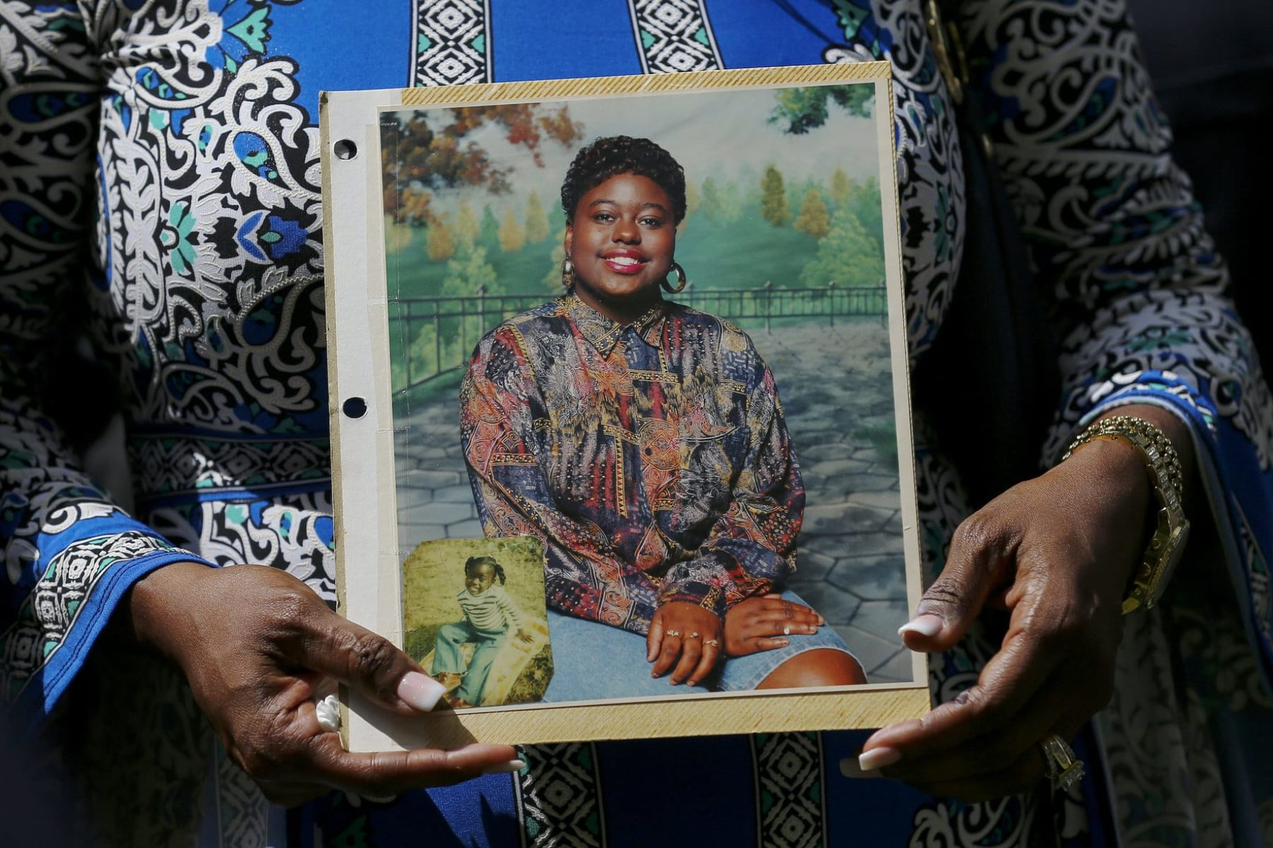 Antoinette Dorsey-James holds a picture of her sister Pamela Turner during a news conference.