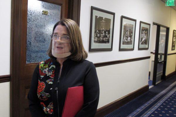 Alaska state Sen. Lora Reinbold, an Eagle River Republican, speaks to reporters in a hallway.