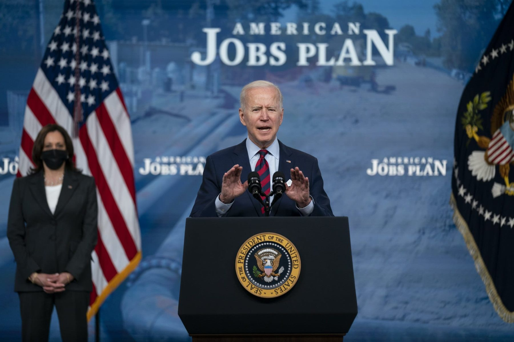 Joe Biden speaking at a podium in front of a backdrop that reads