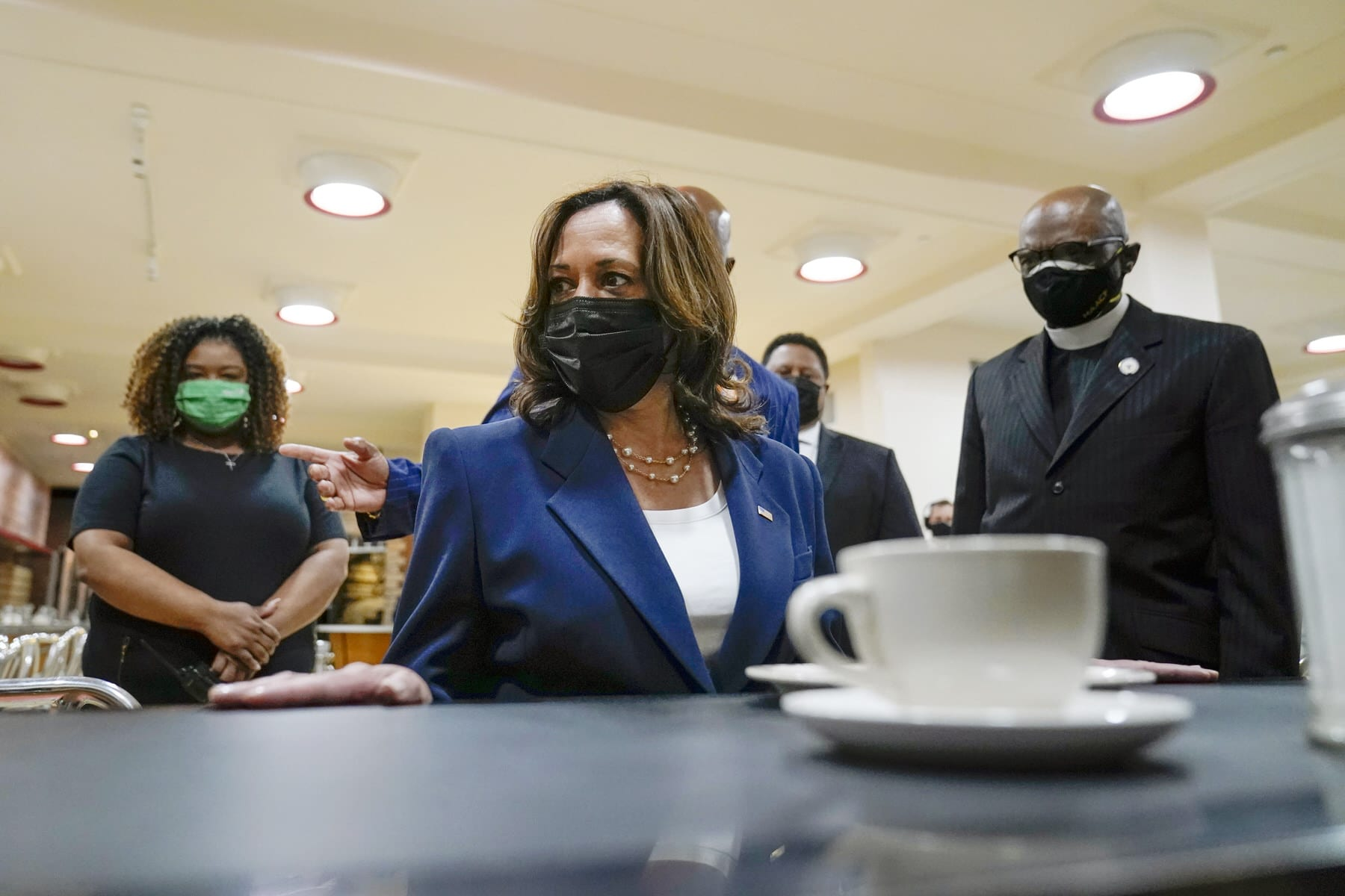 Vice President Kamala Harris sits at the lunch counter as others look on while she visits the International Civil Rights Center and Museum.